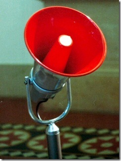 """Electronic red megaphone on stand"" by Adamantios @ Wikimedia"